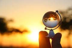 manlig hand som rymmer det lilla crystal jordklotet främst av solnedgång Royaltyfri Foto