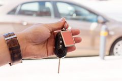 Manlig hand som rymmer en biltangent mot den bruna bilen Royaltyfria Foton