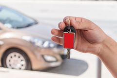 Manlig hand som rymmer en biltangent mot den bruna bilen Royaltyfri Fotografi