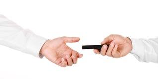 Manlig hand som rymmer en mobiltelefon och över räcker den till andra Arkivfoto