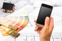 Manlig hand som rymmer en smart telefon över konstruktionsplan Arkivbilder