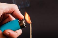 Manlig hand som rymmer en tändare med flamman och ljus en match royaltyfria foton