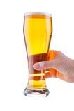 Manlig hand som rymmer ett exponeringsglas av öl Royaltyfria Bilder