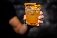 Manlig hand som rymmer ett exponeringsglas av den nya orange alkoholdrycken Royaltyfri Fotografi