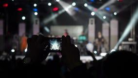 Manlig hand som rymmer rekord- konturer för musikband för videokamerazoomSmartphone Live Concert Performance Taking Photo musik arkivfilmer