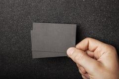 Manlig hand som rymmer två svarta affärskort på arkivfoton