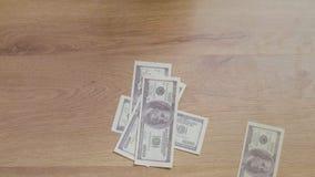 Manlig hand som sätter dollarräkningar på tabellen stock video