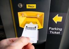 Manlig hand som sätter in parkeringsbiljetten på den elektroniska maskinen royaltyfria foton