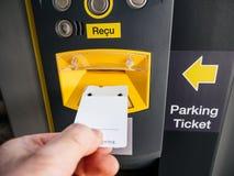 Manlig hand som sätter in parkeringsbiljetten på den elektroniska maskinen royaltyfria bilder