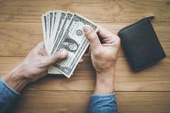 Manlig hand som spela golfboll i hål pengardollarräkningen med plånboken på den wood tabellen arkivbilder