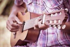 Manlig hand som spelar guitarlele på ängbakgrund Royaltyfri Bild