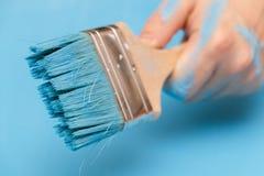 Manlig hand som täckas i målarfärg som rymmer en målarfärgborste royaltyfri foto