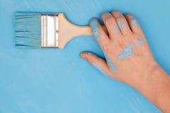 Manlig hand som täckas i målarfärg som rymmer en målarfärgborste arkivbild