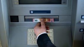 Manlig hand som tar euro från den bästa sikten för ATM som återtar kassa, affärstur royaltyfria foton