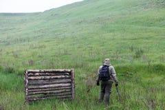 Manlig handelsresande med en yxa och en ryggsäck på en bakgrund av gröna berg och vedträt Royaltyfria Bilder