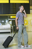 Manlig handelsresande som använder mobiltelefonen av brädet för flygstatus Arkivbild