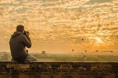 Manlig handelsresande som fotograferar tempel på Bagan Myanmar Asia på soluppgång royaltyfria bilder