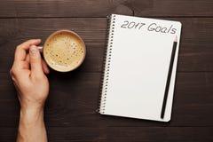 Manlig handhållkopp kaffe och anteckningsbok med mål för 2017 Planläggning och motivation för begreppet för nytt år Top beskådar royaltyfria bilder