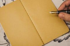 Manlig handhandstil med reservoarpennan på anteckningsboken för kraft papper Special händelse eller tillfälle med kopieringsutrym royaltyfria foton