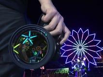 Manlig handinnehavkamera som har att reflektera härligt ljus på linsen med ljus turbinbakgrund arkivbilder