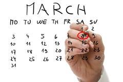 Manlig handmarkering på kalender datumet av mars 8 Royaltyfria Bilder