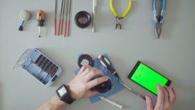 Manlig handreparationslins på grå färgtabellen lager videofilmer