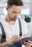 Manlig handstil för bilmekaniker på skrivplattan i seminarium royaltyfria bilder