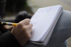 Manlig handstil i anteckningsboken på knäet utanför fotografering för bildbyråer