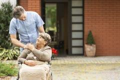 Manlig hjälpande lycklig äldre kvinna i rullstolen framme av huset fotografering för bildbyråer