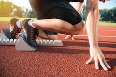 Manlig idrottsman nen på startande position på det rinnande spåret för friidrott arkivbilder