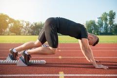 Manlig idrottsman nen på startande position på det rinnande spåret för friidrott Fotografering för Bildbyråer