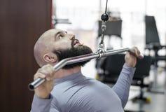Manlig idrottsman nen som gör övningar på pulldownmaskinen i idrottshallen, sund livsstil fotografering för bildbyråer