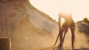 Manlig idrottsman nen som gör push-UPS på stranden och slår repet på jordningen, rund utbildning i solen på det sandigt lager videofilmer