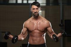 Manlig idrottsman nenDoing Heavy Weight övning för biceps Arkivbild