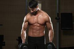 Manlig idrottsman nenDoing Heavy Weight övning för Trapezius Arkivfoton