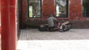 Manlig idrottsman som reparerar hans enduromotorcykel arkivfilmer