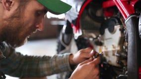 Manlig idrottsman som reparerar hans enduromotorcykel stock video