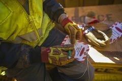 Manlig industriell byggnadsarbetareleverantör som vrida sig information om detaljer på röd och vit faraetikett royaltyfri bild