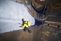 Manlig industriell målare för reptillträdestekniker som arbetar på höjd som hänger på tvilling- rep arkivfoto