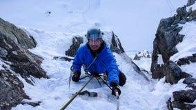 Manlig isklättrare nära slutet av en brant isnedgång i fjällängarna royaltyfria foton
