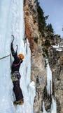 Manlig isklättrare på en brant fryst vattenfall på en härlig vinterdag i de schweiziska fjällängarna arkivbild