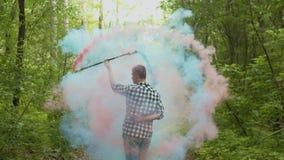 Manlig jonglera färgad röka personal i grönskande skog