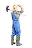 Manlig jordbruks- arbetare som rymmer en skyffel Arkivfoto