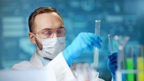 Manlig kemisk tekniker som bär den medicinska skyddande maskeringen, och exponeringsglas som rymmer röret med vikten lager videofilmer