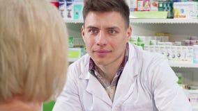 Manlig kemist som lyssnar till hans höga kvinnliga kundförfrågan på medicin stock video