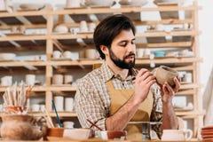 manlig keramiker i förkläde som dekorerar keramik royaltyfria bilder