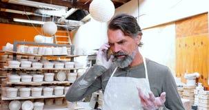 Manlig keramiker som talar på mobiltelefonen 4k lager videofilmer