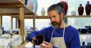 Manlig keramiker som undersöker en lergodsbunke arkivfilmer