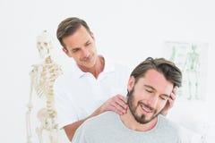 Manlig kiropraktor som gör halsjustering arkivbilder