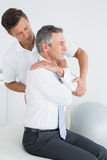 Manlig kiropraktor som undersöker den mogna mannen Royaltyfria Foton